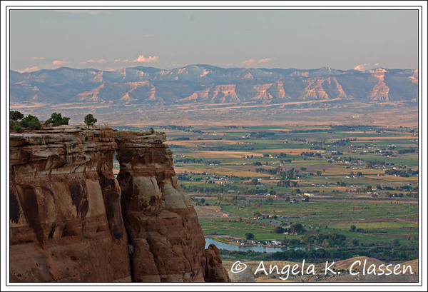 The Book Cliffs glow in the distance, with Window Rock visible in the foreground, at Colorado National Monument