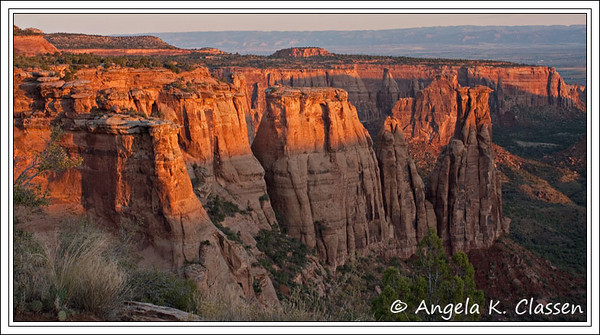 Sandstone monoliths glow at sunrise in Monument Canyon at the Colorado National Monument