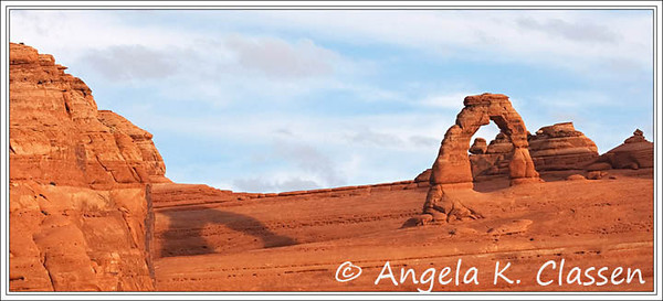 Delicate Arch plays peek-a-boo with its shadow, shot from the lower viewpoint across the canyon
