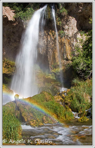 A rainbow dances in the mist created by the spray from Rifle Falls