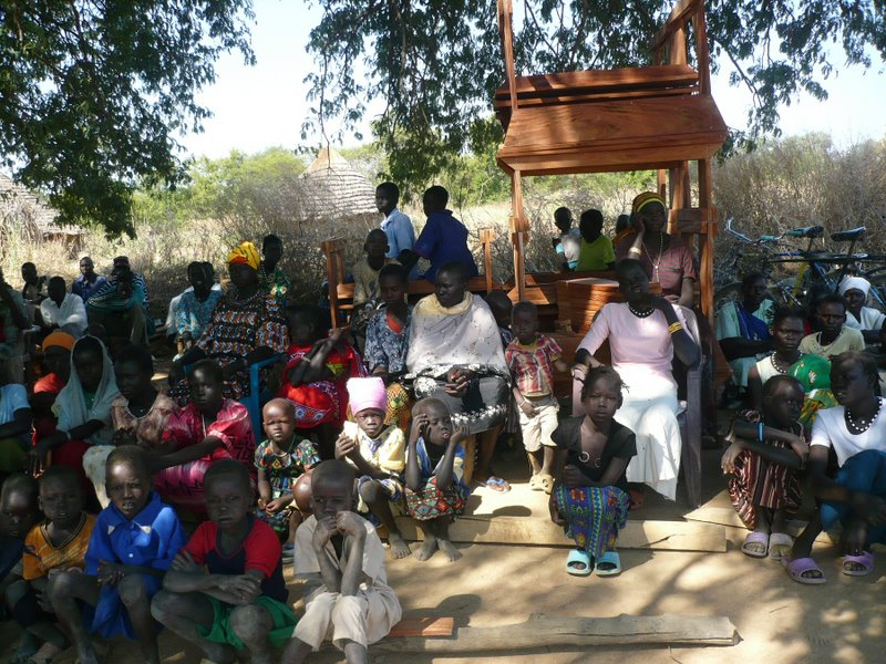 Children and elders have gathered under the trees with the new school furniture!