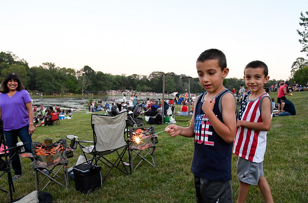 070417  Wesley Bunnell | Staff  4th of July celebrations at Stanley Quarter Park.  Twins Joshua, middle, and Jayden Poudrier have fun with sparklers.