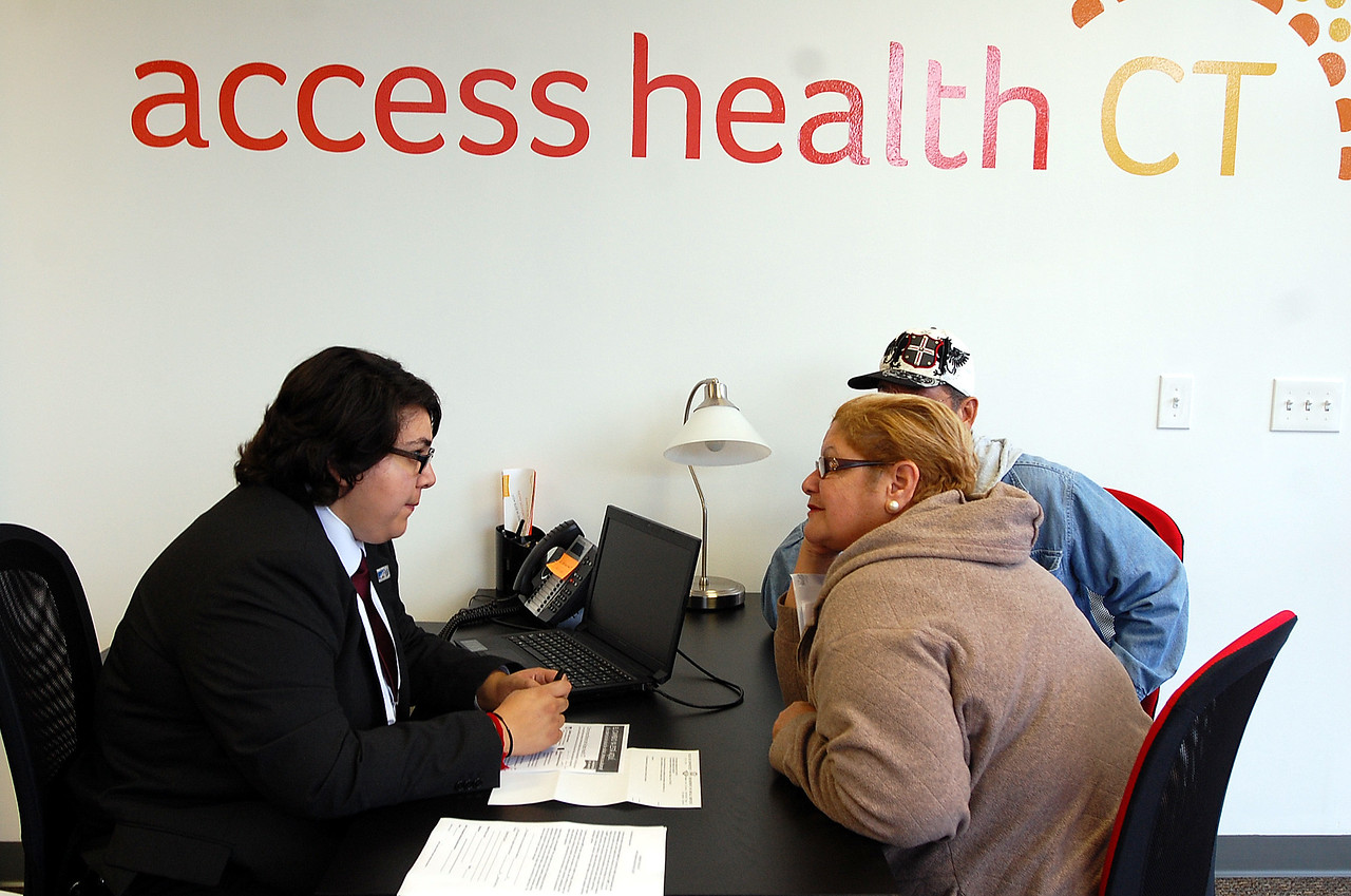Johnny Burnham | StaffGildred Ortiz of Naugatuck, right, registers for insurance at Access Health CT in New Britain Thursday morning with the helpl of Cristela Solorio Ruiz.