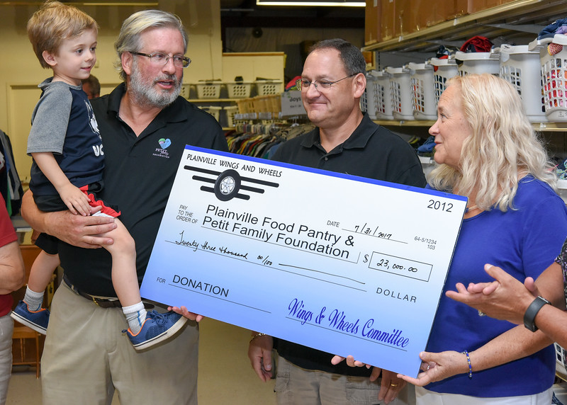 073117  Wesley Bunnell   Staff  Plainville Wings and Wheels presented a check to benefit the Plainville Community Food Pantry and the Petit Family Foundation on Monday evening at the Plainville Community Food Pantry.  Representative William Petit Jr. holds son William Petit III as they stand next to Wings and Wheels Committee member Scott Saunders and President of the Board of Directors for the Plainville Community Food Pantry Maggie Carlin.