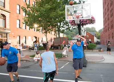 080117  Wesley Bunnell | Staff  The New Britain Police Department hosted their annual National Night Out event in downtown New Britain on Tuesday night. The night featured activities, demonstrations and giveaways including a barbecue to encourage residents to help stop crime. School Resource Officer Jerzy Chmura, L, tracks down a rebound as Nathan Rodriguez, age 13, shoots over fellow School Resource Officer Robert Gomez.