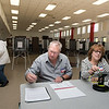 11/7/17  Wesley Bunnell | Staff  Official Checkers Ron Field and Beverly Dube use the new Poll Pad verification system at Slade Middle School on Tuesday morning to check in a voter.