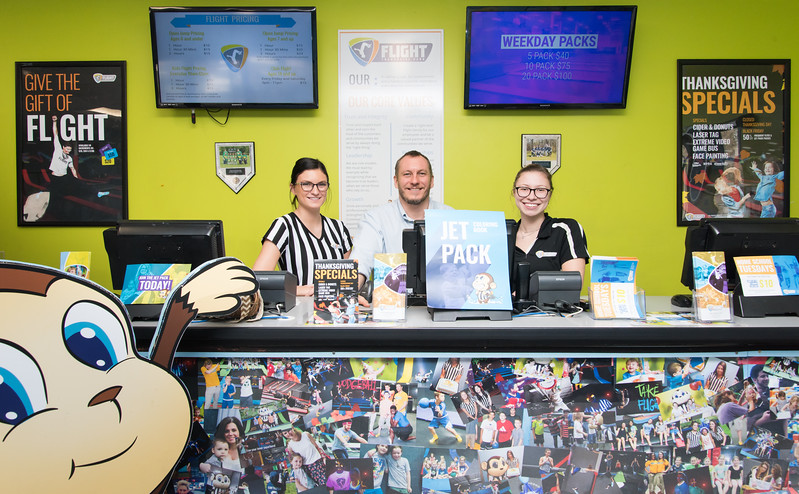 11/20/17  Wesley Bunnell | Staff<br /> <br /> Party Coordinator Savanna Costa, Manager Marcus Diggle and Court Monitor Victoria Tanguay of Flight Trampoline Park in New Britain stand in front of the Wall of Smiles and Flight's mascot Jet.