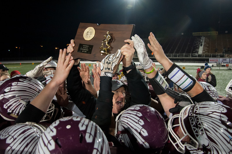12/11/17  Wesley Bunnell | Staff<br /> <br /> The Killingly Redmen capped off an undefeated season by defeating the Joel Barlow Falcons in the Class M Football Championship Monday evening at Veterans Stadium. Killingly coach Chad Neal holds up the championship plaque as he is crowded by players.