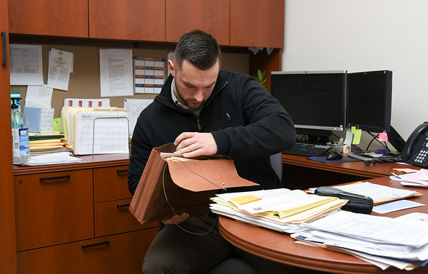011317  Wesley Bunnell | Staff<br /> <br /> New Britain Police Detective Dave McDermott sits at his desk in the records department looking through a case file from 1991.