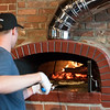 03/30/18  Wesley Bunnell | Staff<br /> <br /> 5 Churches Brewing held their ribbon cutting with city officials on Friday at noon to a crowd of customers lined down the sidewalk. James Cox cooks individual pizzas in the brewery's brick oven.