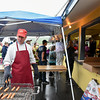 052517  Wesley Bunnell | Staff<br /> <br /> The Berlin High School Upbeat Club held their annual picnic at the Berlin Fair Grounds on a soggy Thursday May 25. Volunteer Rich Crowe grills hot dogs for the stand as crowds line up behind him.
