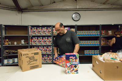 051917  Wesley Bunnell | Staff  Ronald Abbruzzese helps stock shelves with cereal at the HRA Food Pantry in Osgood Heights Park on Friday afternoon.