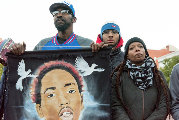 10/24/18  Wesley Bunnell | Staff  A rally was held at Central Park on Wednesday evening calling for the release of police video from the December 14 2017 New Britain Police shooting which resulted in the death of Zoe Dowdell of Bloomfield. Father Shawn Dowdell holds a painted banner with the likeness of his son Zoe as he stands next to his wife Deanna Dowdell.