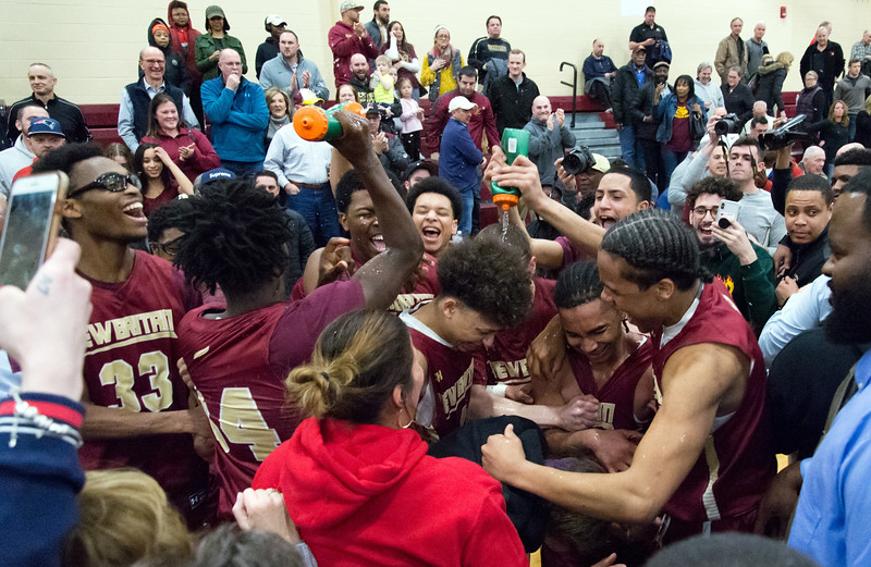 03/12/19  Wesley Bunnell   Staff  New Britain basketball defeated Glastonbury 56-53 in state semifinal game to advance to the championship game to be played this Saturday or Sunday at the Mohegan Sun Casino. Players spray water on each other in celebration.