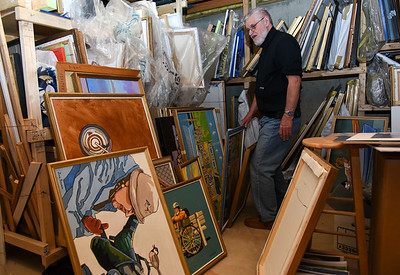 012517  Wesley Bunnell | Staff  Artist John Bower sorts through various paintings and photographs stored in his basement.