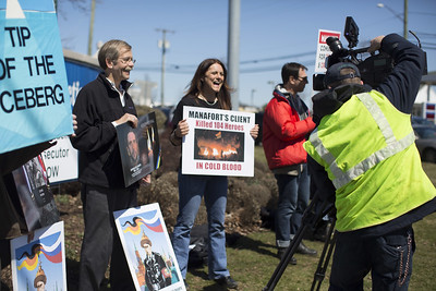 04.02.17 Christopher Burns | Special to the Herald Alex Kuzma, of Glastonbury, on left, and Katja Kolcio, of Haddam, spoke to a TV station during a protest against former Trump campaign adviser Paul Manafort, a New Britain native, on Sunday, April 2.