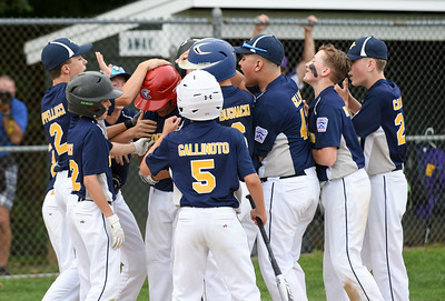 072817  Wesley Bunnell | Staff  Newington vs Ellington in a Little League state finals game played at Adams Middle School in Guilford. Gabby Tirado (21), red helmet, is mobbed by teammates after hitting a home run to right.
