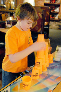 Ethan Thomas practices his cup stacking skills at his fathers restaurant, the Factory, in Ballston Spa. Photo Erica Miller 1/31/11 news_CupStacker2_Tues