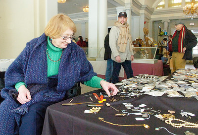 Ellie O'Donnell of Saratoga Springs shops for antiques during Saturday's Winter Antiques Show at the National Museum of Dance. Her husband Bill, admires African art behind at right. Ed Burke 1/29/11