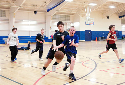 Matthew Triola, center right, makes a move to try and steal the ball from opponent Dakota Harvey in a basketball game Friday during the Kids Night Out youth program at the city recreation center on Vanderbilt Avenue. Ed Burke 1/28/11
