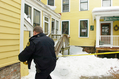 Saratoga Springs police officer Ed Lewis cordons off part of 6 Franklin Square that was damaged Saturday by falling ice which can be seen behind. Ed Burke 1/29/11