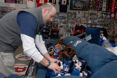 General Manager at The Stadium, located inside the Wilton Mall near Old Navy, Wayne Frankey organizes some of his Giants and Patriots nick-nacks in their store for the upcoming Superbowl this Sunday. Photo Erica Miller 1/30/12 news_Superbowl1_Tues