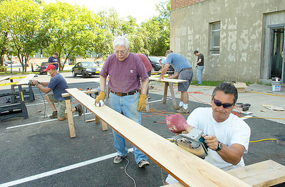 John Watson, right, and Ed Lenz work with other volunteers Saturday to sand bleacher seats from the school's gymnasium. After a coat of varnish the seats will shine along with the gym floor wich has also been refinished. Ed Burke 7/31/10