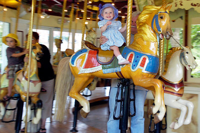 Eleven month old Courtney Smith rides the carousel with the support from her grandfather Bill Murnane, of Saratoga, Friday morning. Photo Erica Miller 7/30/10  new_CongressPark1_Sun