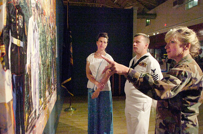 "Artist Rumara Jewett's with her painting called ""Coming Home"" as it is hung at the Saratoga NYS Military Museum on Lake Avenue along side two of her models Lt. Colonel Kimberly Terpening, of the Airforce National Guard, and Jim Savaria, Petty officer 1st of the Navy. Photo Erica Miller 7/30/10 news_ComingHome3_Sat"