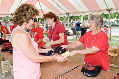 Marge Dennis gets two hats from Marie Childs at Saratoga Race Track Sunday afternoon as part of the weekly giveaway. Photo Eric Jenks 7/31/11