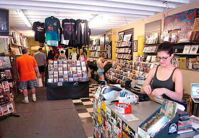 Divinyl Revolution owner Brittany Nasser opens mail as customers browse music selections. Ed Burke 7/30/11