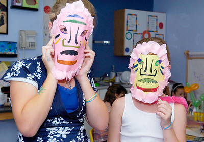Sisters Katie Hutton, 12 left, and Lilly, of East Greenbush, show off their newly designed masks at the Kickoff for Summer Party at the Children's Museum at Saratoga Monday afternoon. Photo Erica Miller 6/28/10 news_SummerParty1_Tues