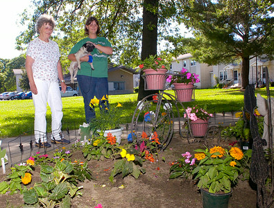 Pat Kail, left, and neighbor Jennifer McGowan admire Kail's flower display Tuesday afternoon outside Kail's Vanderbilt Terrace apartment. The display which includes a patriotic tricycle adorned in red, white and blue flowers has been the target of minor vandalism which has kept Kail up at night trying to catch those responsible. Ed Burke 6/29/10