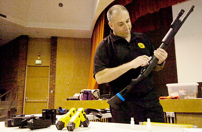 Saratoga Springs Police Department Investigator Sergeant John Catone demonstrates how to load a shotgun during their training at at the Saratoga Springs High School Wednesday morning. Photo Erica Miller 6/30/10 news_sspdTraining3_Thurs