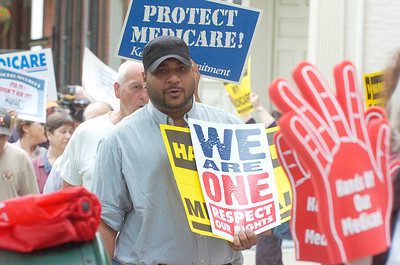 Protesters march on Broadway during a demonstration Wednesday at Congressman Chris Gibson's office. Representatives of several groups gathered to oppose cuts to Medicaid, Medicare and Social Security. Ed Burke 6/29/11