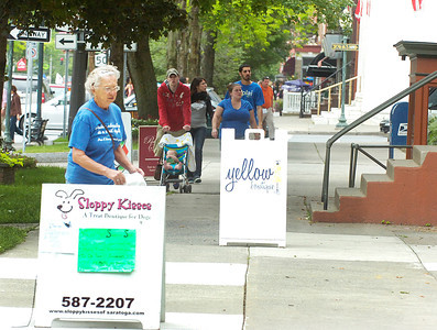 Pedestrians negotiate a maze of sandwich board signs advertising businesses along Broadway in Saratoga Springs. Ed Burke 6/29/11