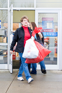 Lynn Saltsman comes out with Black Friday Goodies after her third trip through the stores. Photo Eric Jenks 11/26/10