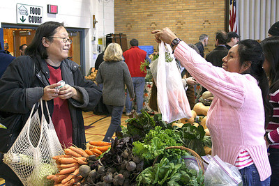 Farmer Valentina Gomez sells carrots to Jean Fei Saturday at the Saratoga Farmers' Market at Divistion Street Elementary School in Saratoga Springs.  Gomez and her family operate the Gomez Veggiville farm near Mechanicville at Hemstreet Park.  Alexander Spinelli 11/27/10