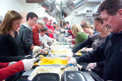 Volunteers create an assembly line in the kitchen of the Presbyterian New England Congregational Church Thursday morning creating Thanksgiving plates to be delivered in the County. Photo Erica Miller 11/25/10 news_Thanksgiving2_Fri