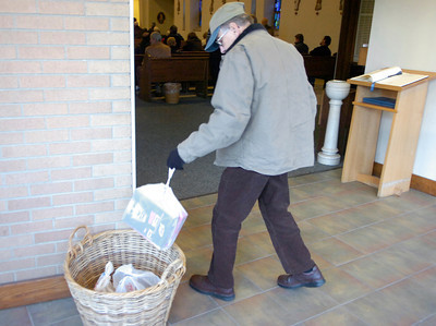 Robert Giordano, a parishioner at St. Clement's Catholic Church, leaves a donation of food for the needy as he arrives for Saturday afternoon mass. Ed Burke 11/27/10
