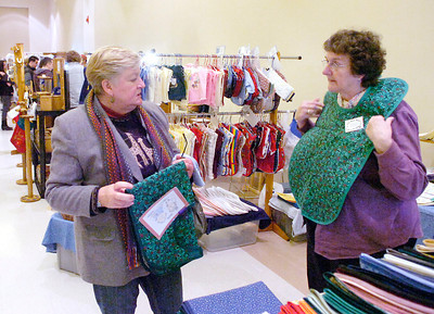 "Cynthia Sheehan of Rutland displays one of her hand-sewn bibs which she calls ""adult cover-ups"" to shopper Pat Everest during Saturday's annual craft fair at the city center that benefits the Saratoga Center for the Family. Sheehan estimates she has sewn 45,000 of the bibs. Ed Burke 11/27/10"