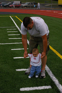 Thursday, August 24th, 2006: Future Athlete, 6-month-old, Steele Kegarris examines the new artificial turf of Schuylkill Haven Rotary Field.  He is assisted by his dad, Dave.  Will we be seeing him in a few years playing high school football on this same field?