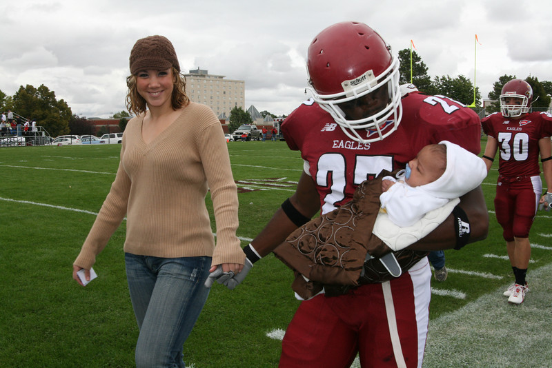 Taivon Harris, baby son of Stephanie Levi and Anton Harris, gets an escort to Elliott Field as his father and other Chadron State College football players were announced with their families Saturday. (Photo by Justin Haag)