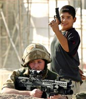 An Iraqi boy plays with a toy gun behind a British soldier during clashes with Shi'ite militia near the local office of the radical Shi'ite cleric Moqtada al-Sadrin the southern city of Basra, September 18, 2004. British troops raided an office used by supporters of rebel Iraqi cleric Moqtada al Sadr in the southern city of Basra on Friday, seizing a large quantity of weapons and explosives, a military spokesman said.       REUTERS/Atef Hassan