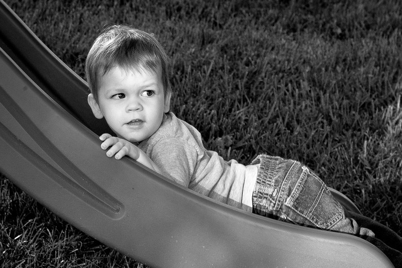 279/365 - October 10, 2012 - Wrong Way Nate <br /> <br /> Now that the kids have a playset in the backyard, my photo opportunities with the kids have increased.  I captured Nate in his favorite way to go down the slide, feet first on his belly.   This photo made me a little sad, as he looks so much older than I perceive him.