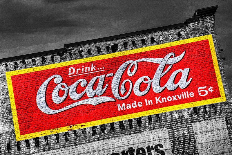 89/365 - April 3, 2012 - Drink...Coca-Cola <br /> <br /> On my way home this evening, I made a detour through downtown.  Prior to turning onto Central Avenue from Broadway, I saw this painted Coca-Cola sign on one of the old brick constructed buildings on Central.  After making a U-turn, I captured this shot peering over top of a chain link fence standing on the running board of the Sequoia.
