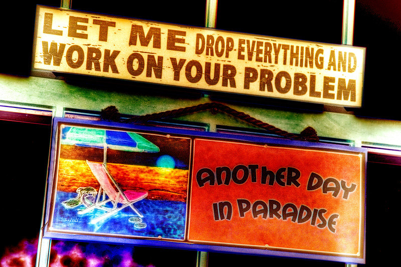 "134/365 - May 18, 2012 - Let Me Drop Everything<br /> <br /> While on vacation, Lisa found the ""Let Me Drop Everything..."" sign in a beach shop and surprised me with it.  She said this would go perfectly in my office at work since it pretty much describes a typical day of mine at the office.  I decided to place it just above a previously purchased ""Another Day in Paradise"" sign, which is my facetious motto while at work.  I used a preset negative curve treatment on the photo for a funky color arrangement."