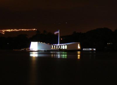 Night shot of the USS Arizona memorial in Pearl Harbor.
