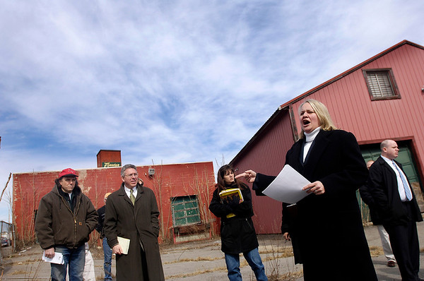 Salem: <br /> Julianna Tache, right, of Tache Real Estate in Salem, auctions off the Flynntan property on Boston Street in Salem Wednesday morning. Tache was hired buy the city to conduct the auction on the cities behalf. Winning the bid was Jon Penni of Boxford, shown left with red hat, next to him is Scott Grover, a local attorney hired by the city for the auction.<br /> Photo by Jim Daly/Salem News. Wednesday, March 22, 2006