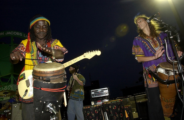 Gloucester: Mamadou Diop of Salem, lead singer of Mamadou, along side band mate Jennifer Millett, play to large crowd at Harbor Loop in Gloucester recently. <br /> Photo by Paul Bilodeau/Salem News. Friday, August 20, 2004